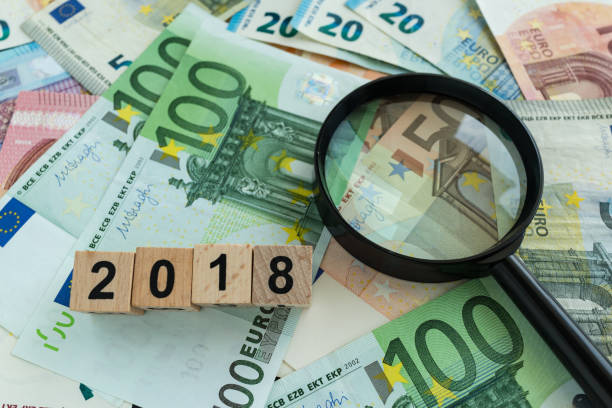 financial tax concept as magnifying glass on pile of euro banknotes and number 2018 on wooden block stock photo