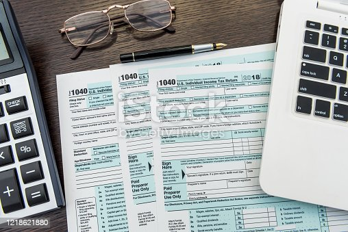184625018 istock photo Financial time tax form with laptop and calculator. Office paperwork 1218621880