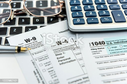 184625018 istock photo Financial time tax form with laptop and calculator. Office paperwork 1222982101