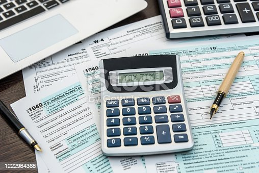 184625018 istock photo Financial time tax form with laptop and calculator. Office paperwork 1222984368