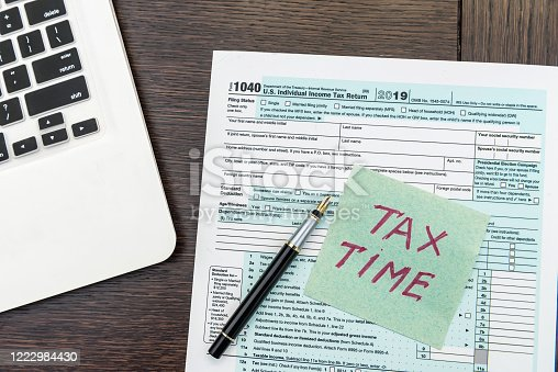 184625018 istock photo Financial time tax form with laptop and calculator. Office paperwork 1222984430