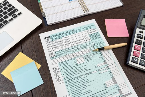 184625018 istock photo Financial time tax form with laptop and calculator. Office paperwork 1253205168