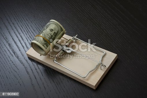 rolled up dollar pile trapped on a mouse trap symbolizing financial problems