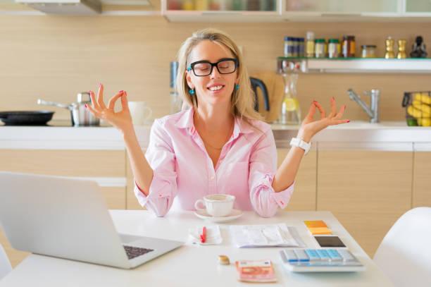 financially free and calm housewife sitting in kitchen - długi zdjęcia i obrazy z banku zdjęć