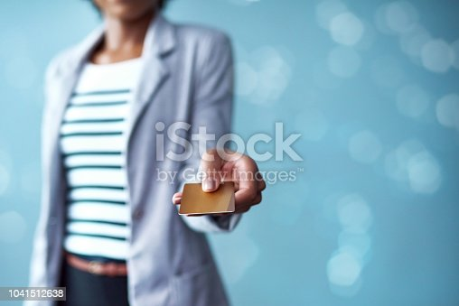 Cropped studio shot of a businesswoman holding a credit card against a blue background