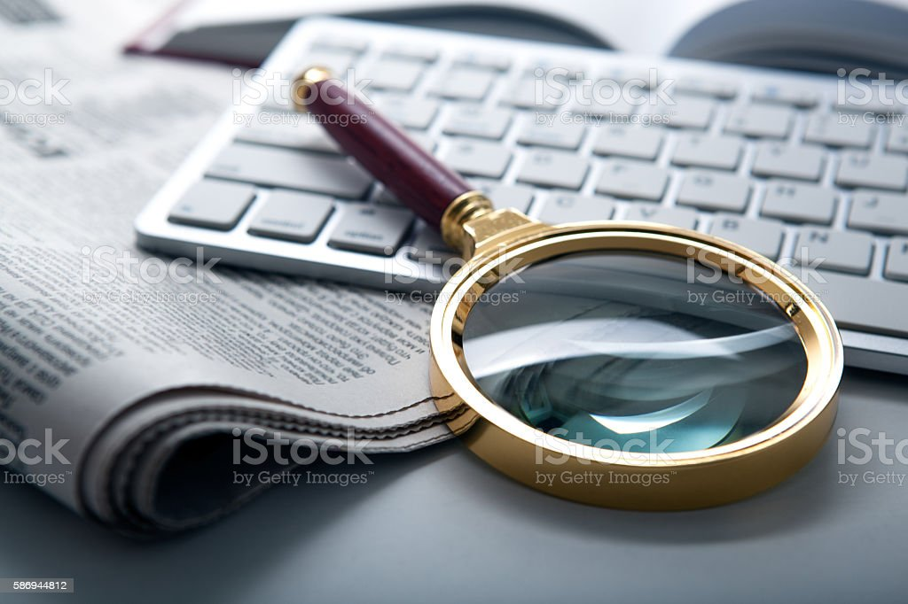 magnifier and newspaper on the keyboard closeup