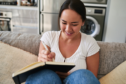 Cropped shot of a young woman writing in a notebook while sitting at home