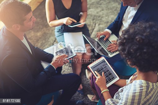 High angle shot of a group of businesspeople using their digital tablets