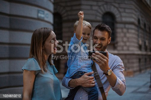 Family with one child outdoors on city street at night. They watching sport game on smart phone and walking in city centre