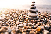 Concept of balance and harmony. rocks on the coast of the Sea in the nature. Photo of Stones pyramid on rocks symbolizing zen, harmony, balance. Ocean at sunset in the background