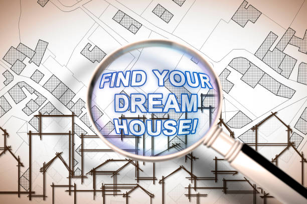 Find your dream house - Searching for a new home concept image with an imaginary city map of territory with buildings and roads through magnifying glass stock photo