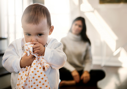 Shot of an adorable baby girl turning away from her mother as she hides behind a cloth