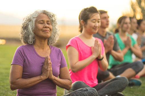 A senior woman of Pacific Islander descent meditates during a group yoga class. She has a slight smile and is seated in the prayer pose. The multi-ethnic group is outdoors. Men and woman of different ages are taking the class. The class participants are seated in a line and they are all doing the prayer pose.