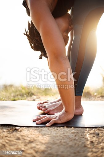 Shot of a fit young female exercising yoga outdoors in nature