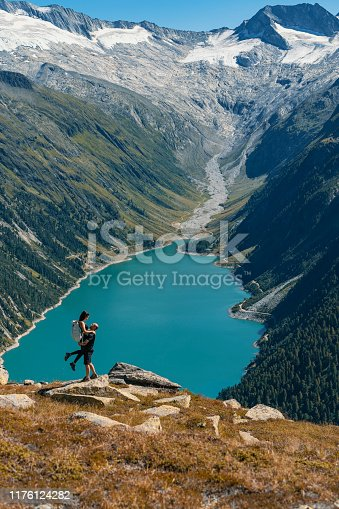 Couple in love enjoying the view from Schlegeis Stausee (Schlegeis Lake) in Tyrol, Austria. Man standing while lifting his girlfriend at Schlegeis glacier and beautiful blue lake in the mountains of Tirol, Austria. Man lifting woman in the air. Happy laughing couple on holiday. Mountain landscape. Boyfriend carrying girlfriend. Romantic moment after proposal or engagement. Passionate lovers on summer vacation.