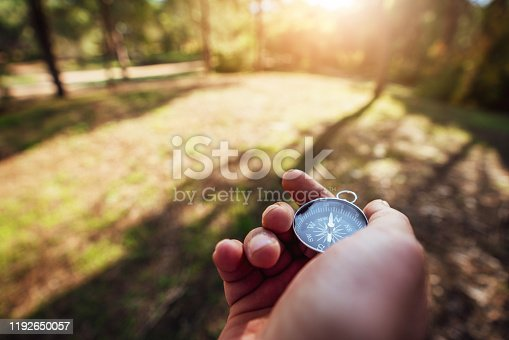 537607438istockphoto finding our way in nature with a compass, looking for the right direction 1192650057