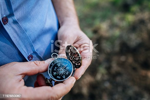 537607438istockphoto finding our way in nature with a compass, looking for the right direction 1192650082