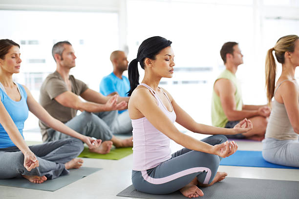 Finding rest and mental relaxation A group of people engaging in yoga meditation during a yoga class yoga class stock pictures, royalty-free photos & images