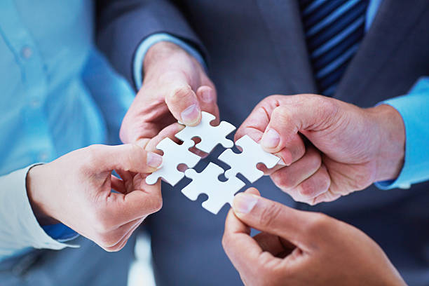 Finding solutions through teamwork A group of business people put together pieces of a puzzle four people stock pictures, royalty-free photos & images