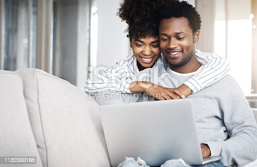Shot of a young couple using a laptop on the sofa at home
