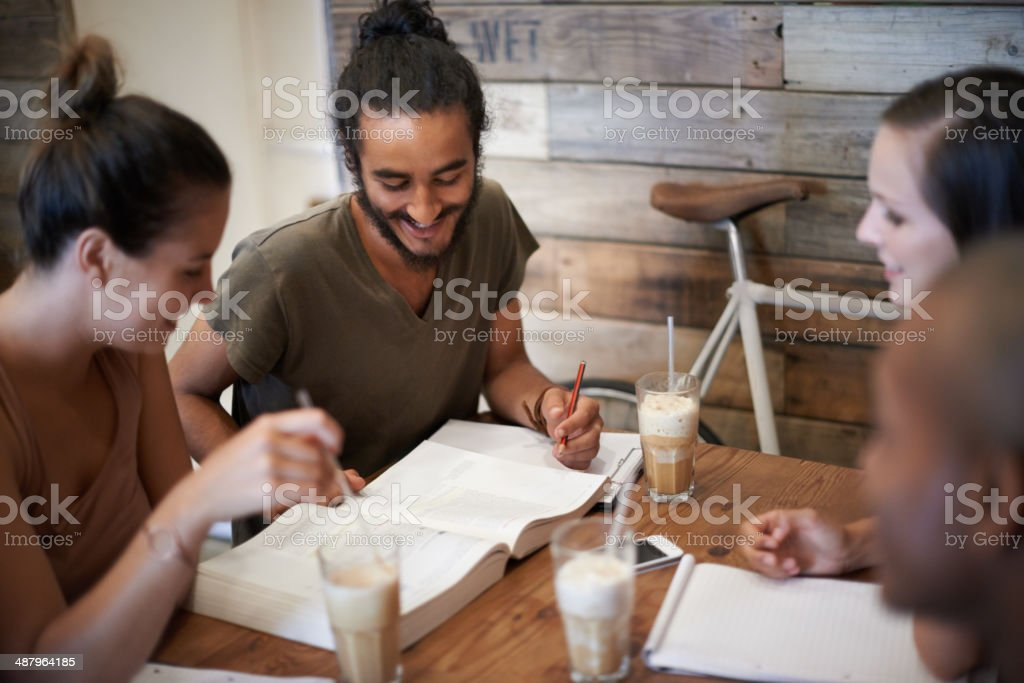 Finding study inspiration from friends Cropped shot a group of friends studying together at a coffee shop 20-29 Years Stock Photo
