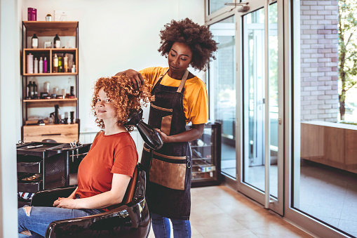 African Hairdresser drying woman's hair with hair dryer in beauty salon.