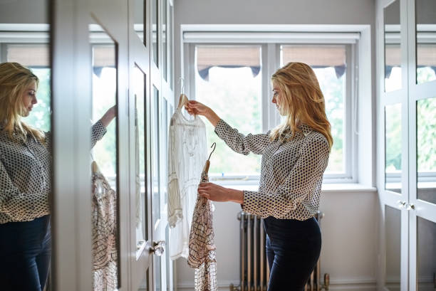 Finding that perfect outfit Shot of a woman getting dressed in a long walk in closet full of mirrors blouse stock pictures, royalty-free photos & images