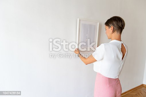 508897972 istock photo Fine adjustment of picture on the wall 1047428134