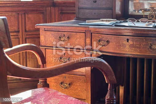 Fine antique pedestal writing desk and chair. Studying history and period drama. Ornate regency table with reading and author materials. Magnifying glass, glasses or spectacles, and fountain pen.