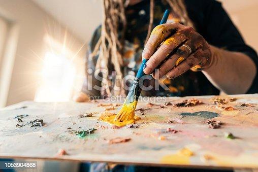937983086 istock photo Fine art painter holding a paintbrush 1053904868