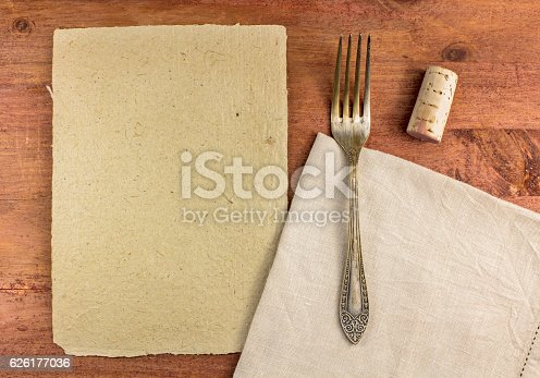 An overhead photo of a piece of parchment for copyspace, with a vintage fork and a cork, on a textile napkin. A restaurant menu or special offer banner design template