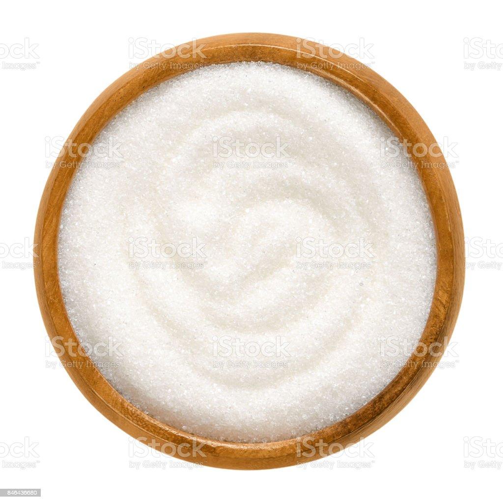 Fine granulated white sugar in wooden bowl over white stock photo