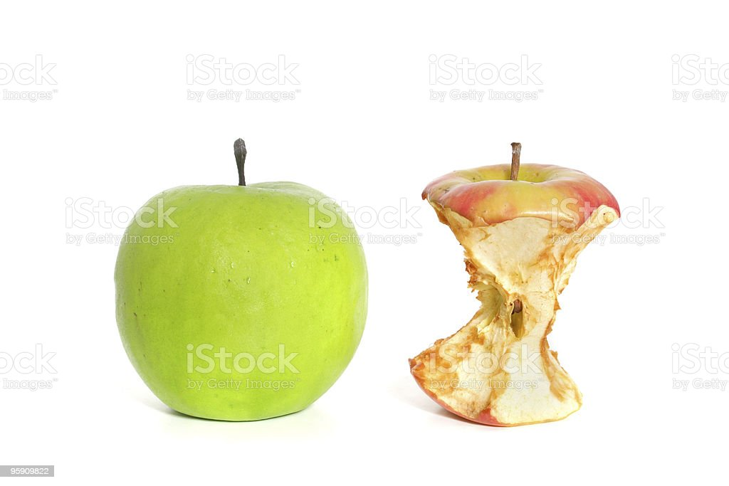 Fine green apple lying next to a rotten one stock photo