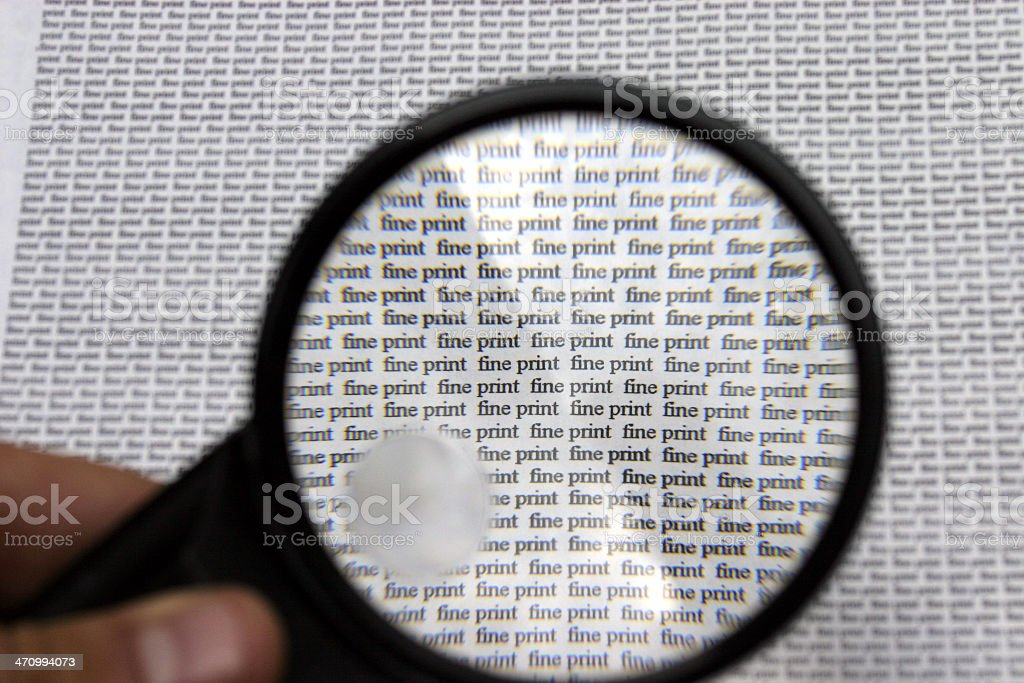 Fine print text viewed thorugh magnifying glass stock photo