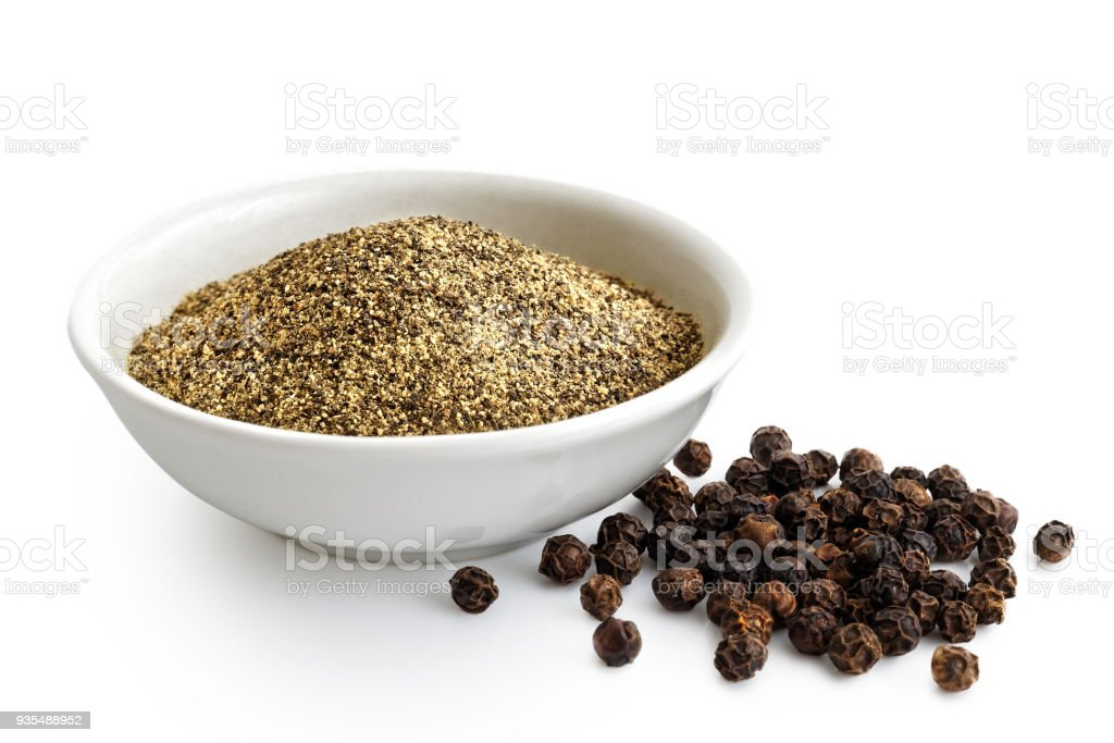 Finely ground black pepper in white ceramic bowl isolated on white. Black peppercorns. stock photo