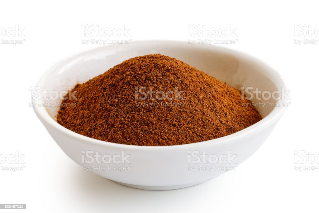 Finely ground cinnamon in white ceramic bowl isolated on white. stock photo