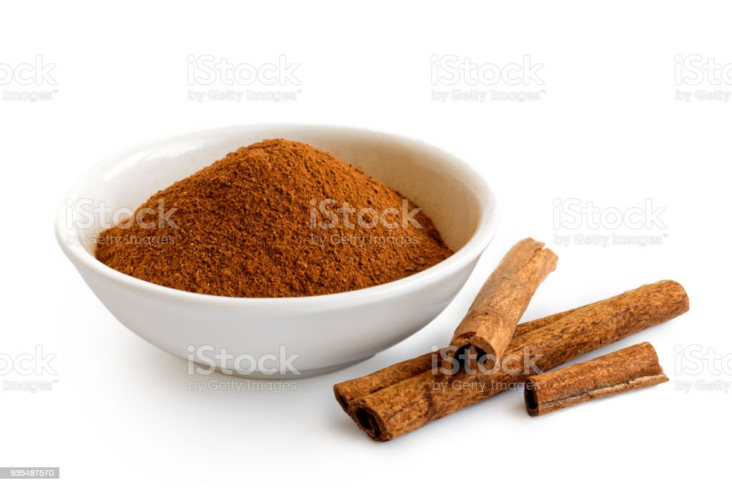 Finely ground cinnamon in white ceramic bowl isolated on white. Cinnamon sticks. stock photo