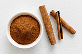 istock Finely ground cinnamon in white ceramic bowl isolated on white wood background from above. Cinnamon sticks. 922791872