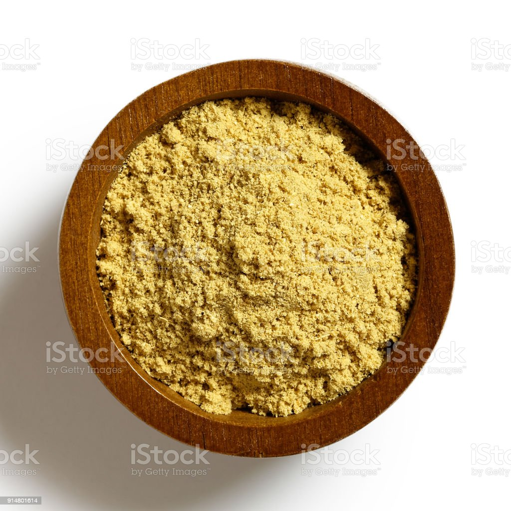 Finely ground dry ginger in dark wood bowl isolated on white from above. stock photo