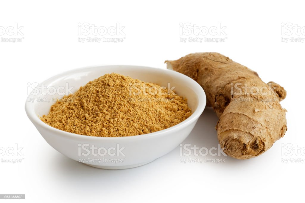 Finely ground dry ginger in white ceramic bowl isolated on white. Fresh whole root ginger. stock photo