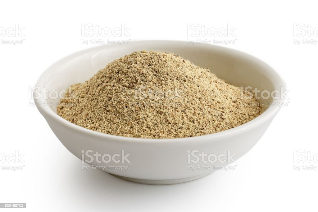 Finely ground white pepper in white ceramic bowl isolated on white. stock photo