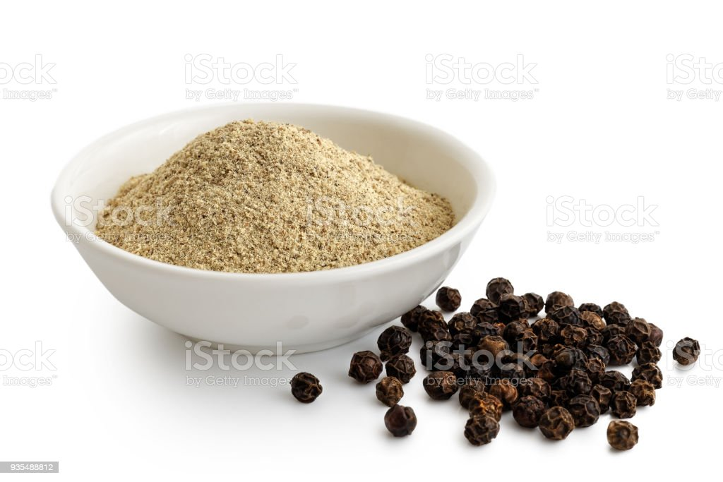 Finely ground white pepper in white ceramic bowl next to black peppercorns isolated on white. stock photo