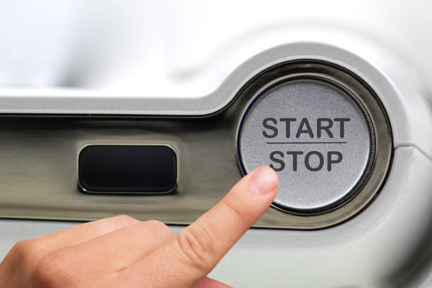 Finger about to press grey start-stop button. Concept for illustration of change or strategic vision, new start, new green economical model, new normal, new mindset,motivational meeting,team building. stock photo