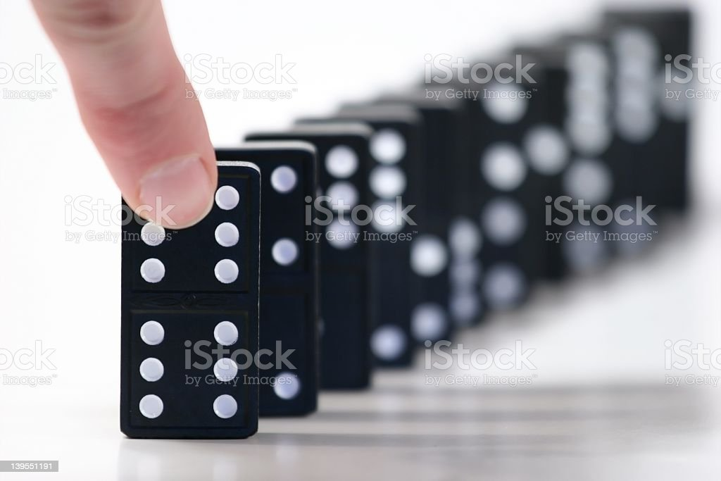 A finger about to push black & white dominoes in a row royalty-free stock photo