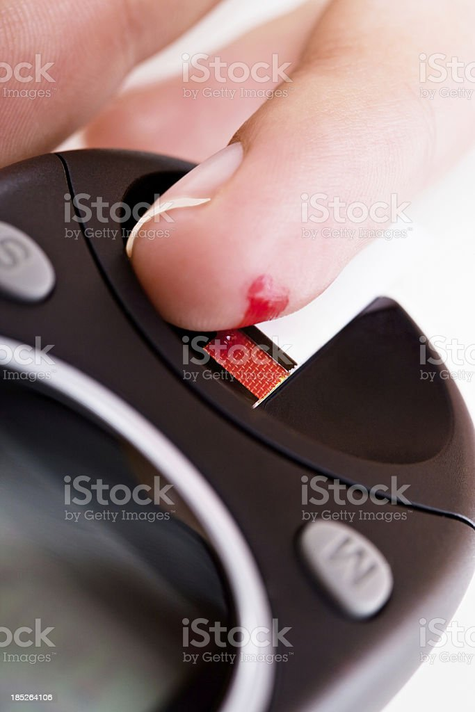 Finger adding blood to glucometer test strip royalty-free stock photo