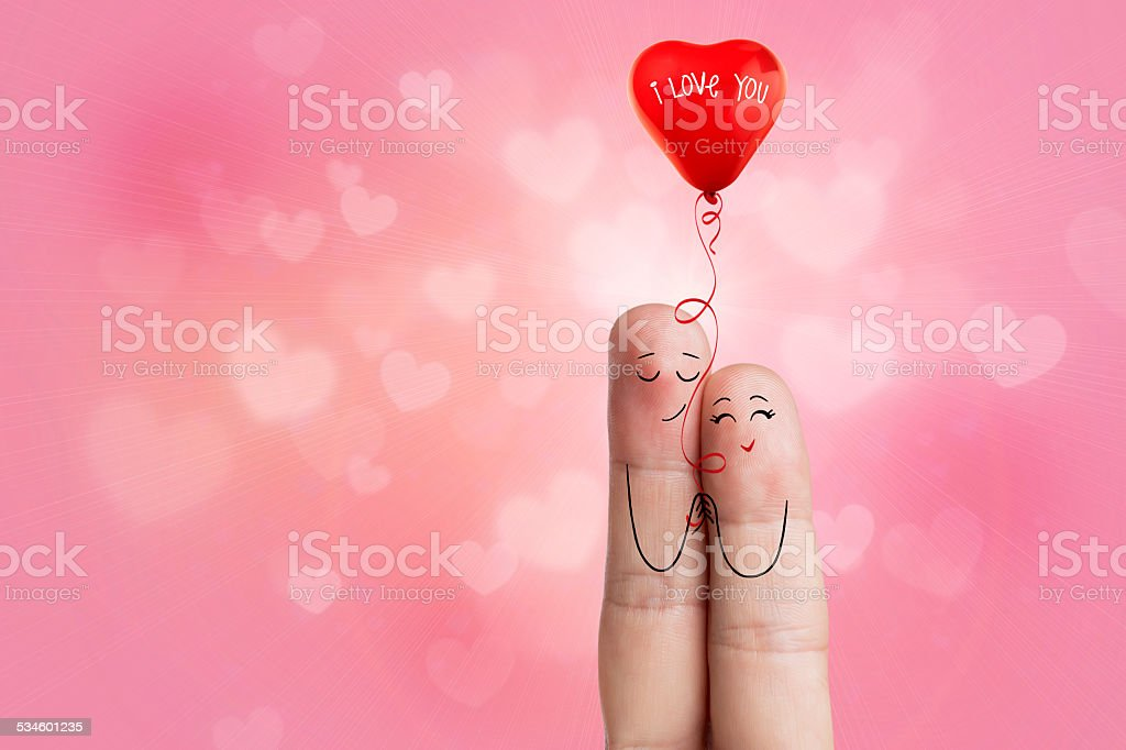 Finger art. Lovers is embracing and holding red heart balloon stock photo