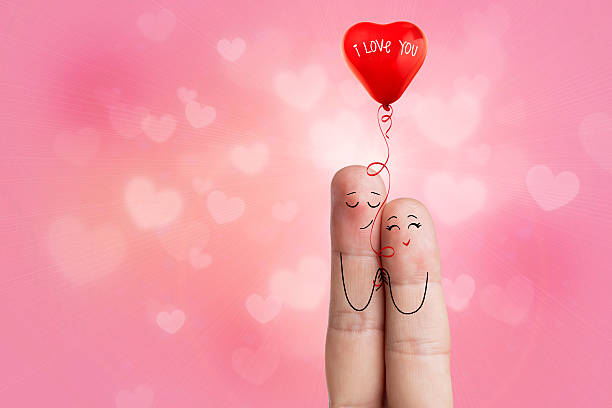finger art. lovers is embracing and holding red heart balloon - welcome march stock photos and pictures