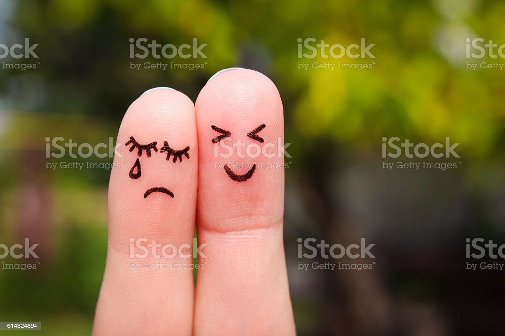 Finger art of couple. Woman cries, man is cheerful. stock photo