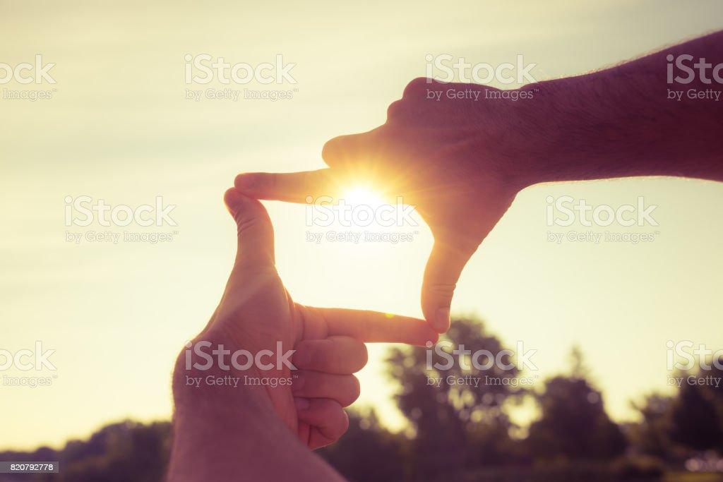 Finger-Rahmen erfassen den Sonnenuntergang - Lizenzfrei Anreiz Stock-Foto