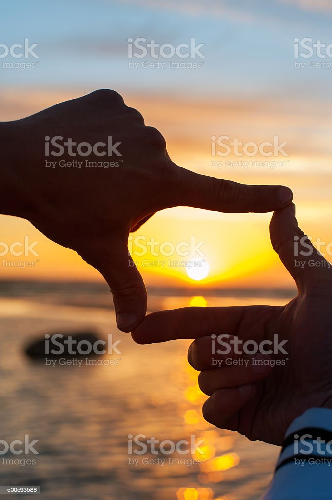 Finger frame-  imitation of capturing rays of sunset sunlight stock photo